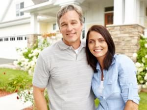 A mature couple standing proudly in front of their home